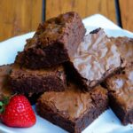 A stack of brownies on a whit plate with a strawberry on the side.