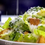Caesar Salad on a white plate with Parmesan cheese sprinkling down on it.
