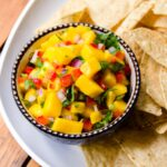 Mango Salsa in a blue bowl on a white platter with tortilla chips.