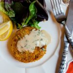 One crab cake with sherry sauce on a white plate with lemon wedges and mixed greens.