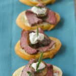 Beef and Mushroom Crostini on a turquoise napkin.
