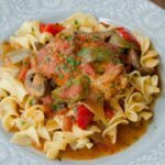 Chicken Cacciatore on a light blue plate with egg noodles.