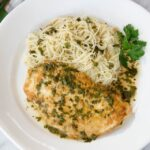Chicken Francaise on a white plate with angel hair pasta.