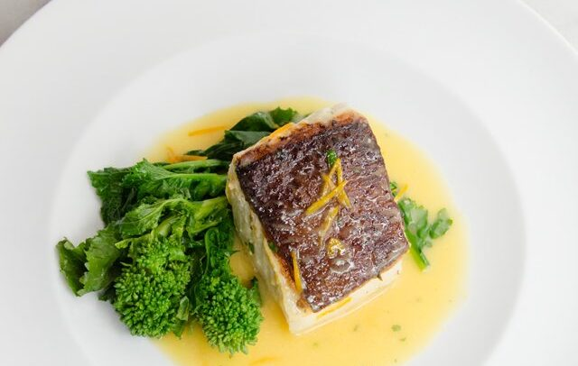 Halibut with orange butter on a white plate with broccoli rabe.