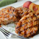 Grilled Pork Chops on a platter with peach BBQ sauce.