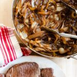 Browned beef on a plate and caramelized onions in a pan -ingredients for beef carbonnade.