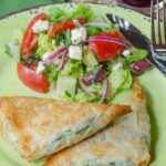 Spinach and Ricotta Phyllo Pockets on a green plate with a side of Greek Salad.