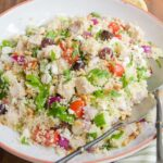 Turkey Couscous Salad in a white bowl on a wooden table.