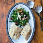 Black cod with grapes, kale and pecans on an oval white plate.