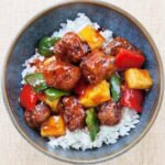 Sweet and sour pork in a blue bowl on a peach placement.