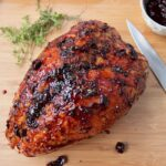Air Fried Turkey Breast with Cherry Glaze on a wooden cutting board with a knife along side.