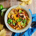 Chicken Tortilla Soup with a blue napkin, spoon, lime wedges and tortilla chips on a wooden table.