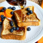 French toast with blueberries and mandarins and maple syrup being poured on top.
