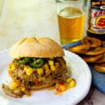 Mango Jalapeno pulled pork sandwich on a white plate with a beer in the background and some chips on the side.