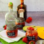 three jars of strawberry-mango margarita jam on a counter with a bottle of tequila and triple sec in the background.