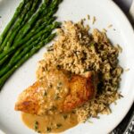Pan Seared Chicken breast with sherry cream pan sauce, rice and asparagus on a white plate.