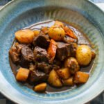 Guinness Stew in a blue bowl on a blue and white checkered placemat.