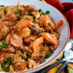 Close up shot of jambalaya in a white bowl with serving utensils and a colorful napkin.