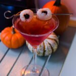 Pama Lychee-tini on a table with little pumpkins behind.