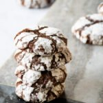 Four chocolate crinkle cookies stacked on each other with other cookies in the background.