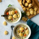 Two bowls of slow cooker chicken pot pie soup with more biscuit croutons on a wooden board and a blue napkin next to it.