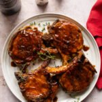Four skillet glazed pork chops on a white plate with a red napkin beside it.