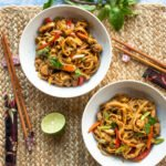 Two bowls of chicken drunken noodles on a placemat with chopsticks, half a lime and fresh Thai basil.