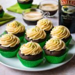 Irish Coffee Cupcakes in green cupcake liners on a plate with a bottle of Bailey's Irish Cream in the background.