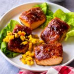Four fillets of salmon with BBQ sauce on them, on a white plate with mango salsa and some lettuce leaves.