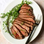 Grilled London Broil, sliced on a white oval platter with fresh thyme and a serving fork.