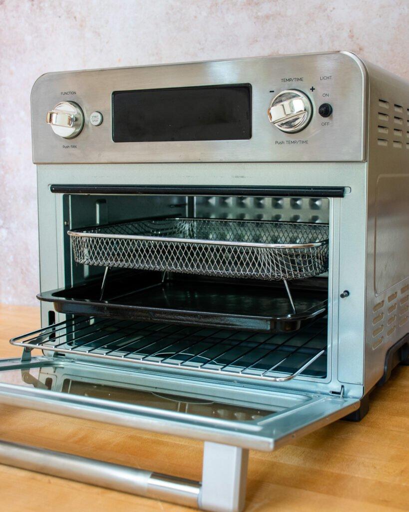 An air fryer oven with door open on a countertop.