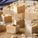 A stack of three squares of peanut butter fudge on a cutting board with more squares of fudge around.