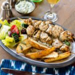 Chicken souvlaki on a plate with Greek potatoes and salad with a place setting on a wooden table.