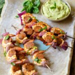 Grilled shrimp chorizo skewers on a large rectangular platter with a dish of green dip.