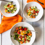 Tomato and Cucumber Salad in a serving bowl with two smaller bowls, orange napkins and forks all on a white table.