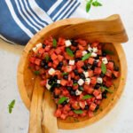 Watermelon feta salad with blueberries in a wooden salad bowl with a blue and white striped towel next to it.